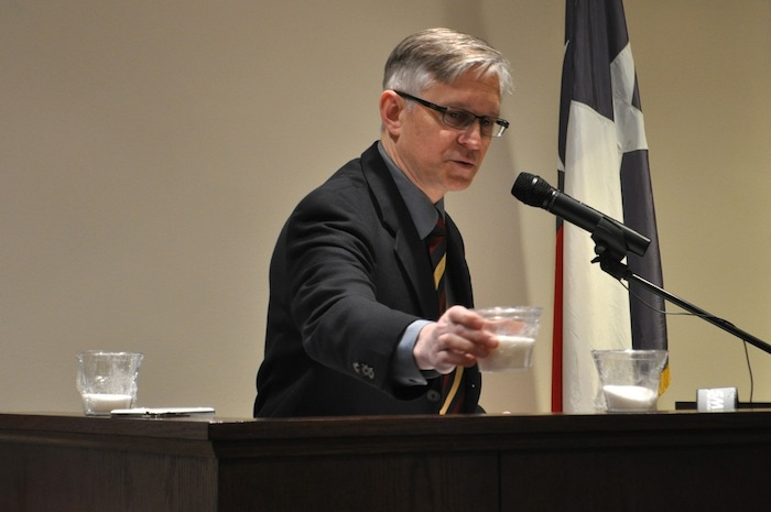 Dr. Bryan Alsip, executive vice president and chief medical officer at University Health System, sets down a cup with 22 ounces of sugar in it (what the average American intakes per day) next to a cup with 12 ounces of sugar in it (what we should have per day). Photo by Iris Dimmick.