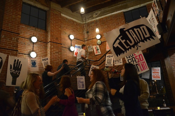 """For their final song, Adam Tutor leads the crowd on a """"train"""" through Rosella and the Snake Hawk Press artwork. Photo by Gretchen Greer."""