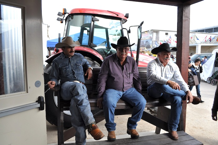 Three men wait for the horse auction to start during the 2013 San Antonio Stock Show and Rodeo. Photo by Iris Dimmick.