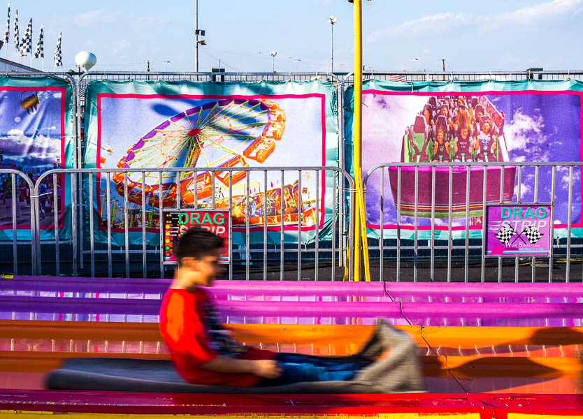 A boy zooms down a large slide at a rodeo carnival.