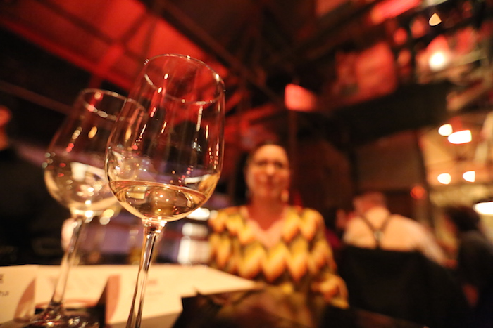 Sommelier Jen Beckmann from Kuhlman Cellars sits in the background of two wine glasses. Photo by Adam Rocha.