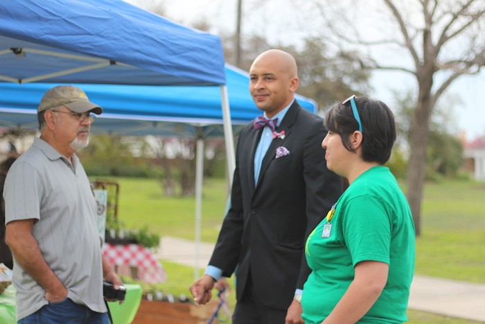 Alan E. Warrick II speaks with Dignowity Hill Farmer's Market founder Michelle Herrera and a market attendee at the grand opening.