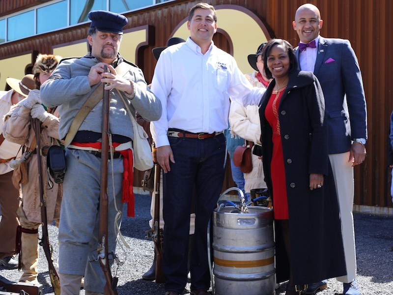 Alamo Beer President and Founder Eugene Simor stands with Mayor Ivy Taylor, Councilmember Alan Warrick II (D2), and Alamo Battle reennactors at the grand opening of the Alamo Beer Company brewery. Photo by Scott Ball, courtesy of Alamo Beer.