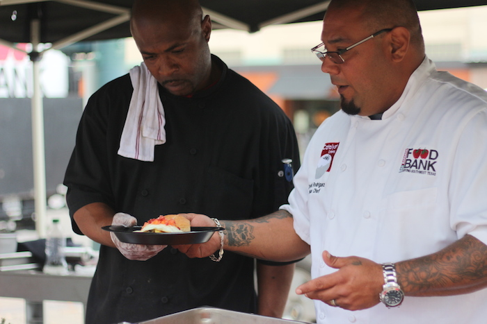 Food Bank employees Davis Rodriguez and Teddy Phillips prepare a meal at the Main Plaza Farmers Market on Tuesday. Photo by Joan Vinson.