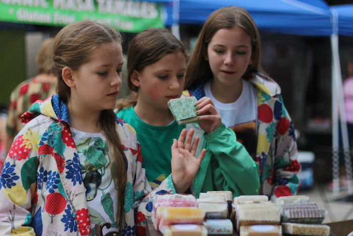 Annabelle Czaruk and sisters Lily and Caroline Watson smell soap at the Soilnature stand at the Main Plaza Farmers Market on Tuesday. Photo by Joan Vinson.