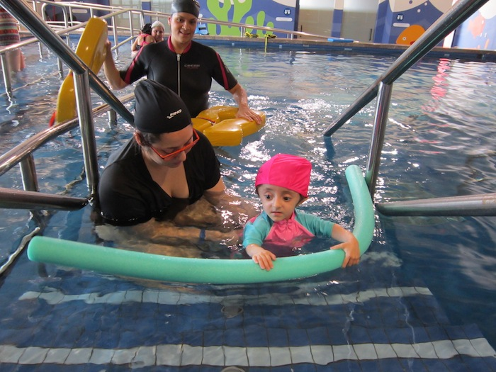 "Four-year-Samantha Haney who was born with a condition commonly known as ""brittle bones,"" enjoys the hydrotherapy pool and the attentions of physical therapist Belinda Flores."