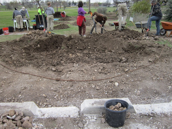 Volunteers dig a basin to change the flow of rain water. Photo by Karen Stamm.