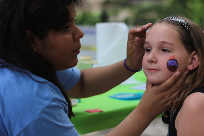 A young girl gets her face painted during the Fiesta Arts Fair. Photo by Joan Vinson.