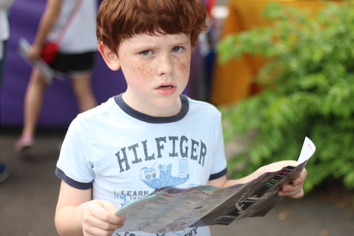 A young boy checks his schedule during the Fiesta Arts Fair. Photo by Joan Vinson.