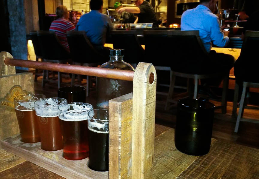 Southerleigh produces a variety of original beer on the grounds, including these four offered as a flight during a preview dinner. The carrier for the beer flight features a carving, a rendition of the Pearl brewhouse. Photo by Mindy Wallen.