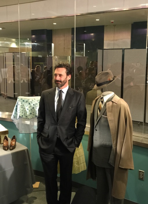 """Actor Jon Hamm stands with an iconic Don Draper suit from """"Mad Men."""" Photo by Gisela Girard."""