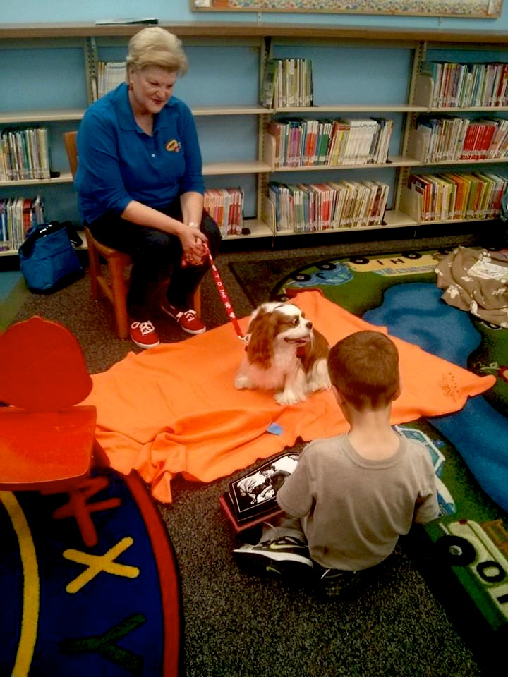 Trained therapy dogs lend their ears to eager readers at Brook Hollow, Guerra, Igo, Pan American and Parman branch libraries weekly. The program allows readers to practice the skill of reading in a fun and relaxing environment. Courtesy photo.