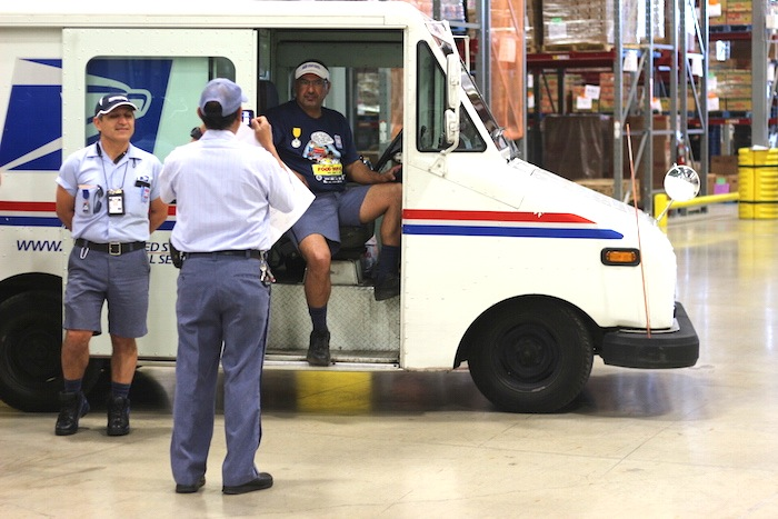 """USPS employees pose for photos during the """"Stamp Out Hunger"""" kickoff event at the San Antonio Food Bank. Photo by Joan Vinson."""