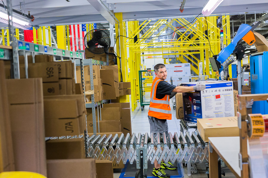 An Amazon worker moves boxes onto shipping rollers at the Amazon Fulfillment Center in Schertz.