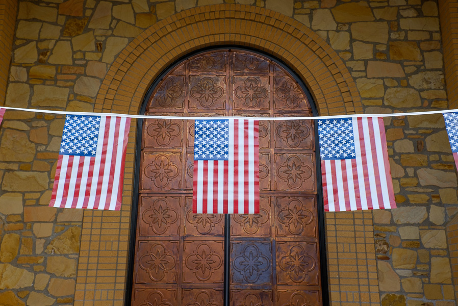 American flags decorate the front doors of Texas A&M University-San Antonio during the mayoral forum. Photo by Scott Ball.