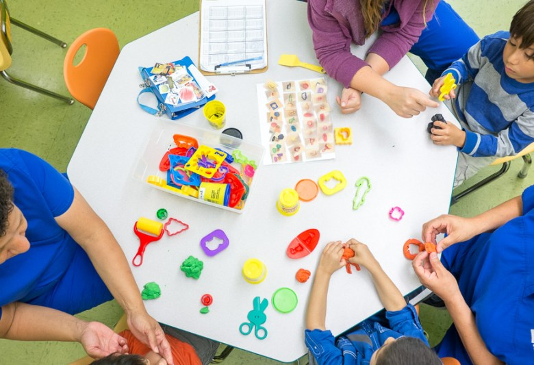 A table is surrounded by children with specialists working with each child at the Autism Treatment Center of San Antonio. Photo by Scott Ball.