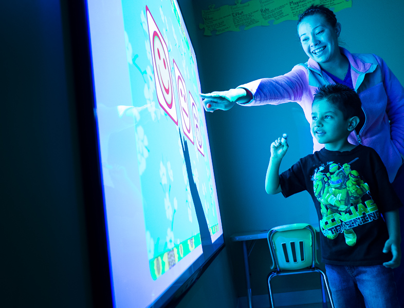 Brittany Morgan and a young boy select a mood on an interactive white board at the Autism Treatment Center of San Antonio.