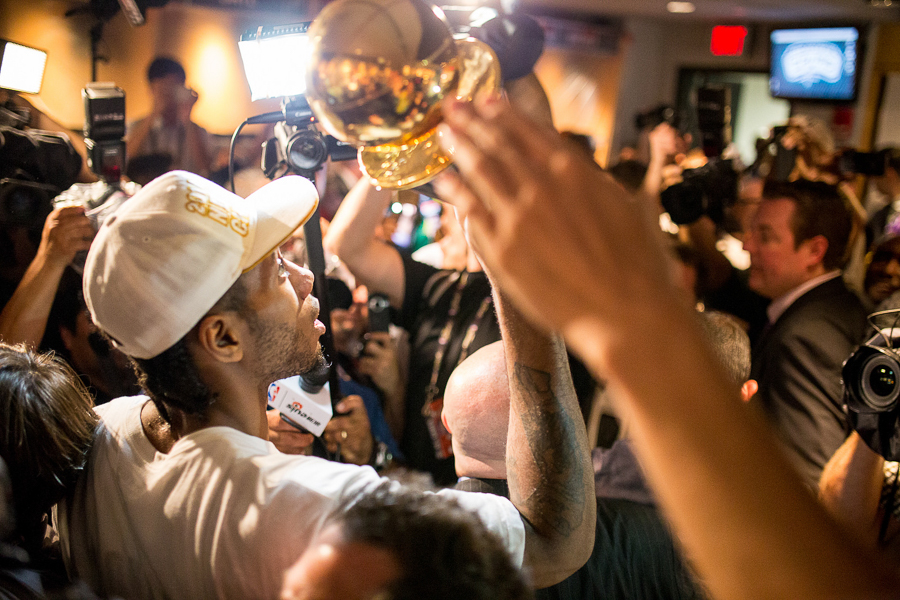 Kawhi Leonard holds his MVP trophy high after the Spurs' win of the 2014 NBA Finals. Photo by Scott Ball.