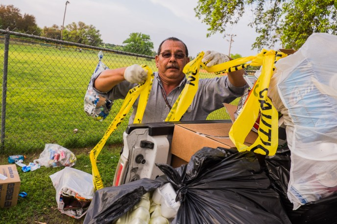Jesse Sabedra of the City of San Antonio gathers garbage in a truck at Breckenridge Park.  Photo by Scott Ball.