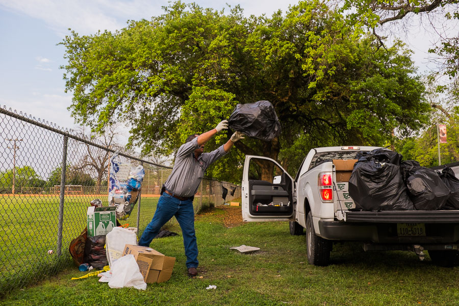 Parks and Recreation employee Jesse Sabedra throws bags of garbage in a truck at Brackenridge Park. Photo by Scott Ball.