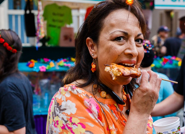 A woman eats something on a stick during NIOSA at La Villita.  Photo by Scott Ball.