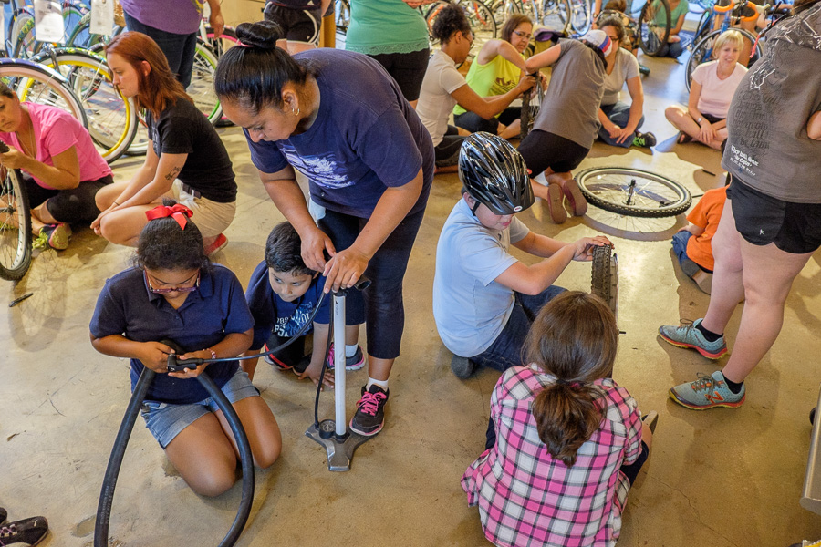 Attendees take their turn to repair a flat during the third Women's Wrench Night at Bike World. Photo by Scott Ball.