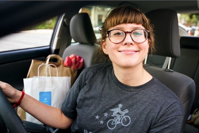 A Postmates driver poses for a photo with bags of deliveries in tow. Photo courtesy of Postmates.