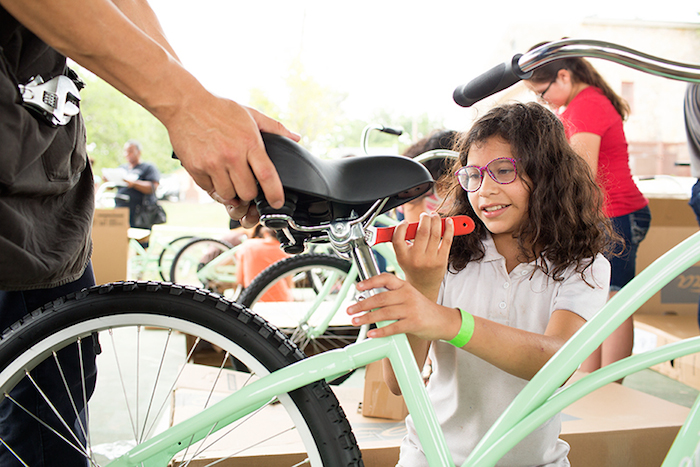 A young woman tightens the seat of her bike during the Chiquitas Ciclistas event in the Eastside. Photo by Rachel Chaney