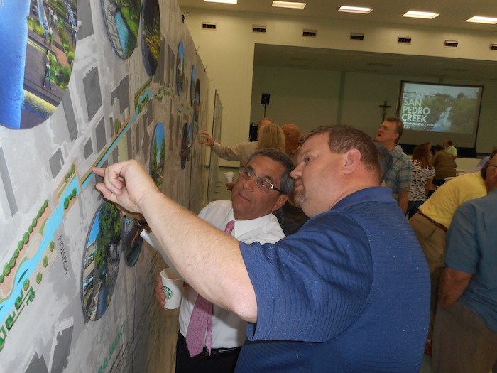 Mark Penner (left) and Russell Persyn of San Antonio River Authority discuss how improvements along San Pedro Creek will affect Penners Men's Specialty Shop. Photo by Don Mathis.