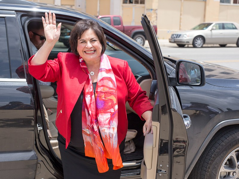 Leticia Van de Putte waves to the crowd as she exits a vehicle. Photo by Scott Ball.
