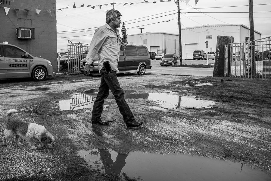 A man walks through the parking lot of Olga's bar. Photo by Scott Ball.