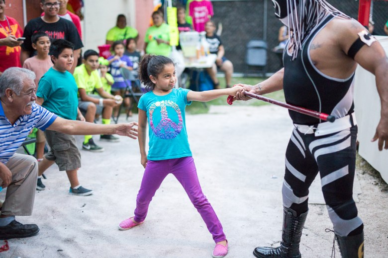 A child takes back her grandfathers cane from a luchador. Photo by Scott Ball.