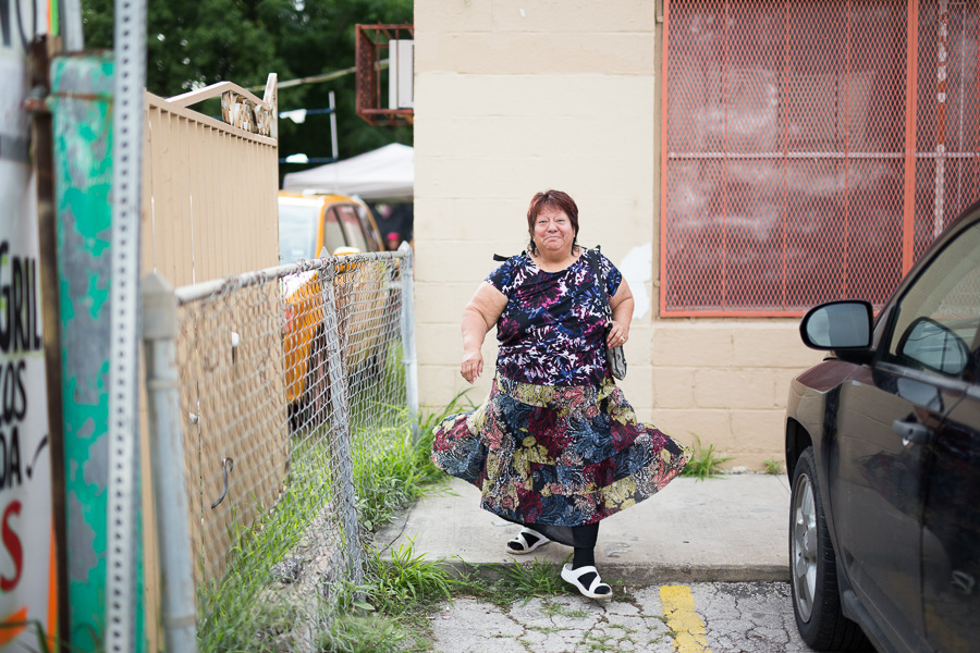 A woman walks through the parking lot of Olga's Bar. Photo by Scott Ball.