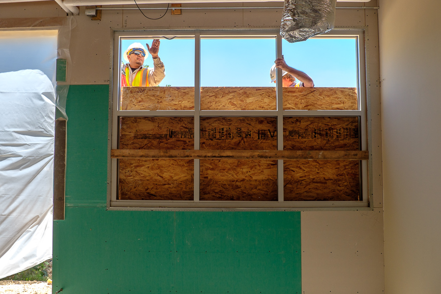 Construction workers prepare framing for a panel of windows at the Sikh Dharamsal Gurdwara of San Antonio.