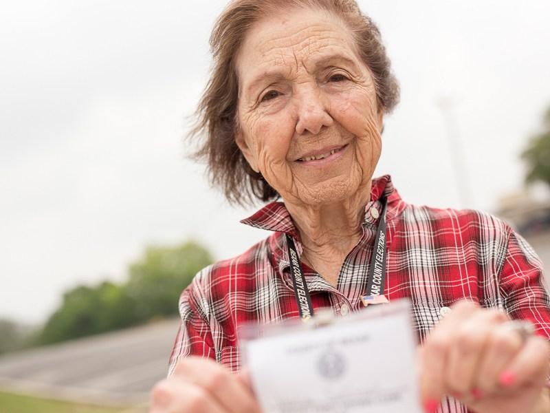 Velia Salinas holds up her voting clerk badge. Photo by Scott Ball.