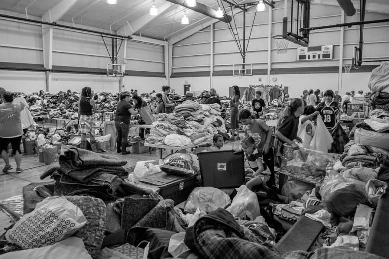 A gymnasium full volunteers sort through donated goods.  Photo by Scott Ball.