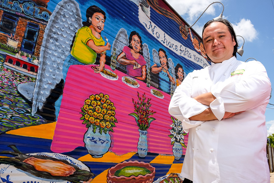 Chef Johnny Hernandez poses for a photo alongside a mural outside of La Gloria. Photo by Scott Ball.