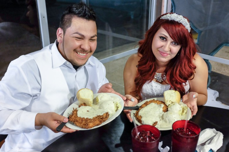 Newlyweds Mark and Morgan Medina hold up fried chicken dinners after their marriage. Photo by Scott Ball.