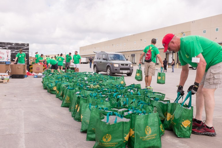 Bags of produce are handed out to families in need of food. Photo by Scott Ball.
