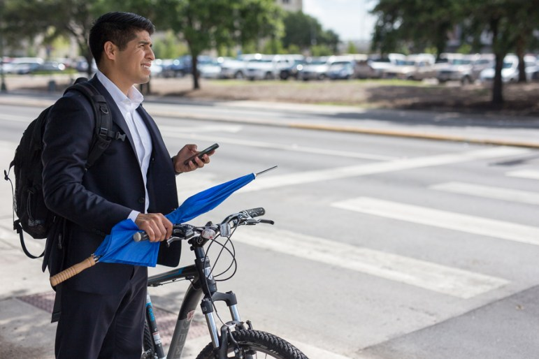Councilman Rey Saldaña looks up to find the location of his next bus stop. Photo by Scott Ball.