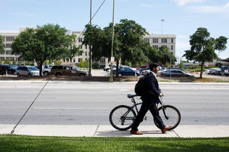 Councilman Rey Saldaña walks his bike to a bus stop. Photo by Scott Ball.