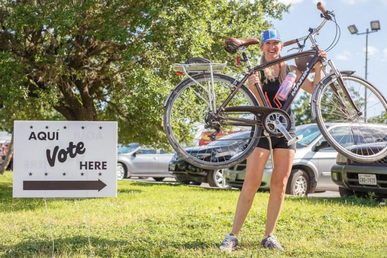 Rachel McDevitt holds her bike up just before voting. Photo by Scott Ball.