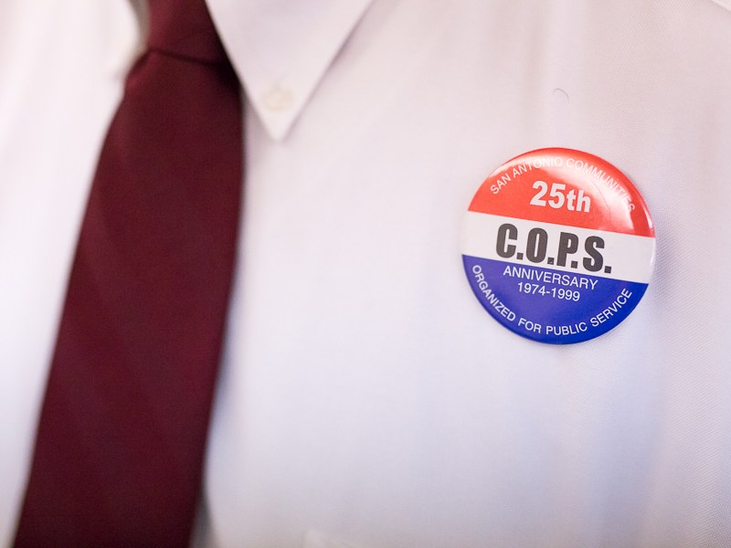A vintage C.O.P.S. button is pinned on a members shirt. Photo by Scott Ball.