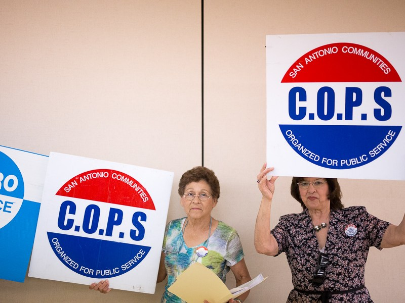 Community members hold C.O.P.S signage. Photo by Scott Ball.