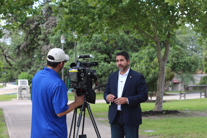 Councilmember Roberto Treviño is interviewed at San Pedro Springs Park on Friday. Photo by Joan Vinson.
