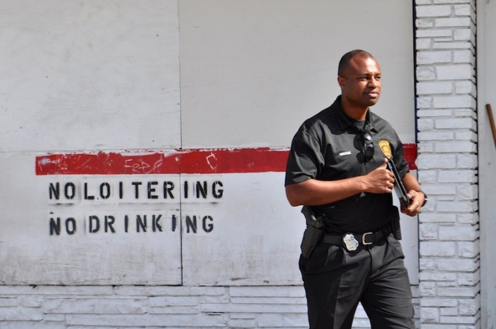 SAPD Officer Douglas Greene walks by the Handy Shop. Photo by Iris Dimmick.