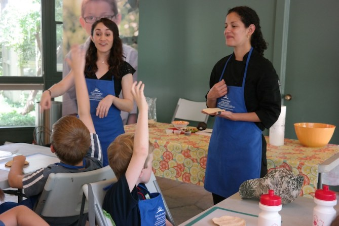 Children raise their hands as dietitian Celina Paras (left) and chef Maria Palma ask questions. Courtesy photo.