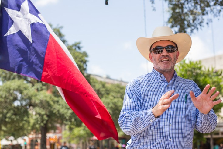 David Watts addresses the crowd while a Texas flag waves behind him. Photo by Scott Ball.