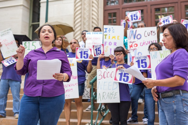 Elsa Caballero speaks in front of city hall backing a $15 minimum wage. Photo by Scott Ball.