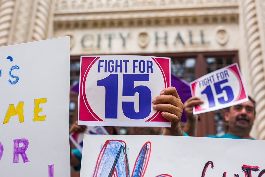 A man holds up a sign in support of a $15 minimum wage. Photo by Scott Ball. A man holds up a sign in support of a $15 minimum wage. Photo by Scott Ball.